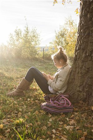 Girl sitting under tree and listening music Stock Photo - Premium Royalty-Free, Code: 6102-08384591