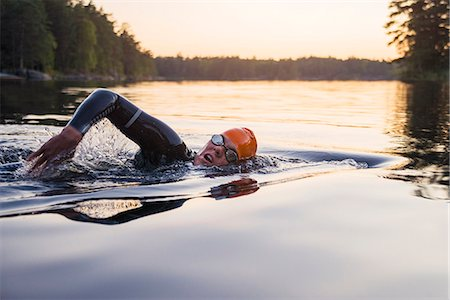 swimming - Person swimming at sunset Stock Photo - Premium Royalty-Free, Code: 6102-08388051
