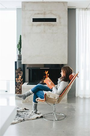 Woman reading book in front of fireplace Stock Photo - Premium Royalty-Free, Code: 6102-08329977