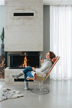 Woman drinking coffee in front of fireplace Stock Photo - Premium Royalty-Free, Code: 6102-08329978