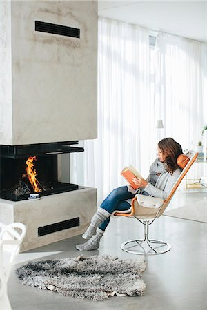 Woman reading book in front of fireplace Stock Photo - Premium Royalty-Free, Code: 6102-08329979