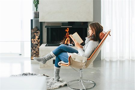 Woman reading book in front of fireplace Stock Photo - Premium Royalty-Free, Code: 6102-08329980