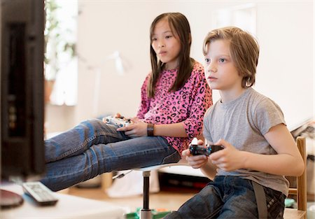Boy and girl playing video game Stock Photo - Premium Royalty-Free, Code: 6102-08330036