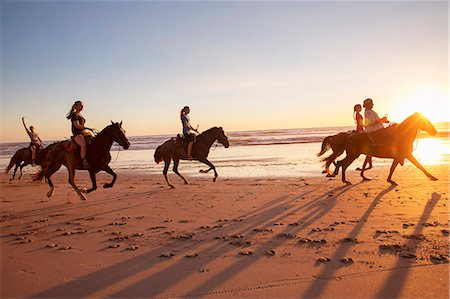 Group of people horseback riding on beach at sunset Stock Photo - Premium Royalty-Free, Code: 6102-08542383