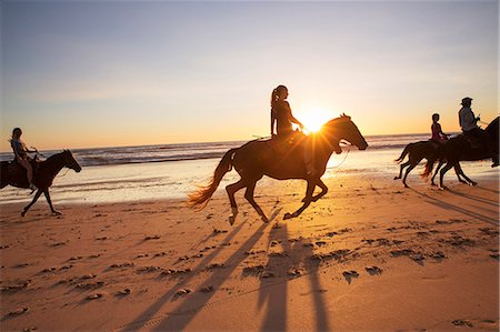 People horseback riding on beach at sunset Stock Photo - Premium Royalty-Free, Code: 6102-08542382