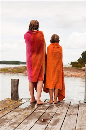 preteen girls bath - Two girls wrapped in towels standing on jetty Stock Photo - Premium Royalty-Free, Code: 6102-08558797