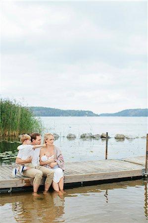 Family sitting on jetty Stock Photo - Premium Royalty-Free, Code: 6102-08566499