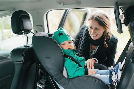 Mother with putting baby son in car seat Stock Photo - Premium Royalty-Free, Code: 6102-08566817