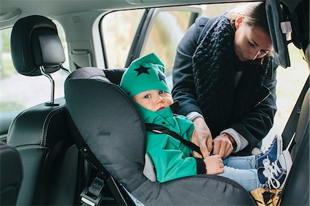 Mother with putting baby son in car seat Stock Photo - Premium Royalty-Free, Code: 6102-08566818