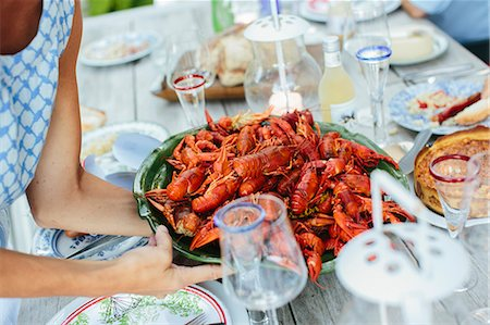 eating - Mature woman placing bowl of crayfish on table Stock Photo - Premium Royalty-Free, Code: 6102-08520874