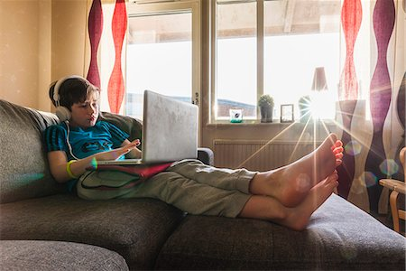 Boy using laptop at home Stock Photo - Premium Royalty-Free, Code: 6102-08520833