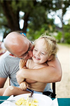 father son shirtless - Father kissing laughing son Stock Photo - Premium Royalty-Free, Code: 6102-08746348