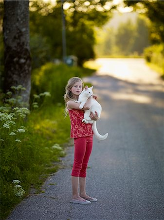 preteen girl pussy - Smiling girl on road with white cat Stock Photo - Premium Royalty-Free, Code: 6102-08746440