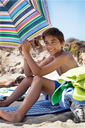 preteen boy shirtless - Smiling boy sitting on beach Stock Photo - Premium Royalty-Free, Code: 6102-08746497