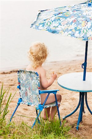 Little boy sitting on chair at beach Stock Photo - Premium Royalty-Free, Code: 6102-08746640