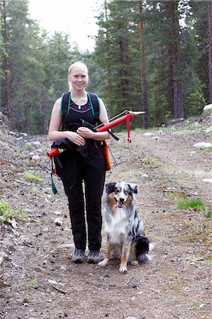 Smiling young woman with dog in forest Stock Photo - Premium Royalty-Free, Code: 6102-08760394