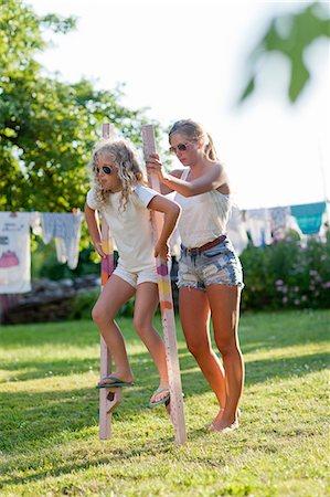 Sisters walking on stilts in garden Stock Photo - Premium Royalty-Free, Code: 6102-08760697