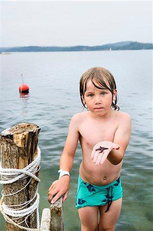 Boy on jetty holding starfish Stock Photo - Premium Royalty-Free, Code: 6102-08761466