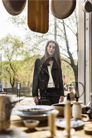 Young woman looking at shop window Stock Photo - Premium Royalty-Free, Code: 6102-08726835