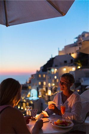 santorini island - Women playing cards at dusk Stock Photo - Premium Royalty-Free, Code: 6102-08885141