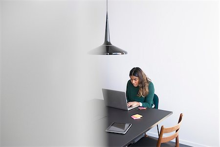 Woman working on laptop in office Stock Photo - Premium Royalty-Free, Code: 6102-08942362
