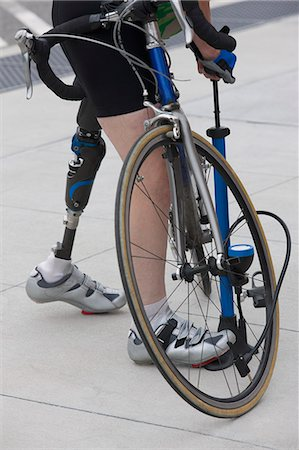 Woman with a prosthetic leg pumping air into a bicycle Stock Photo - Premium Royalty-Free, Code: 6105-05396398