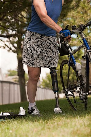 Woman with prosthetic leg preparing for bike race Stock Photo - Premium Royalty-Free, Code: 6105-05396318