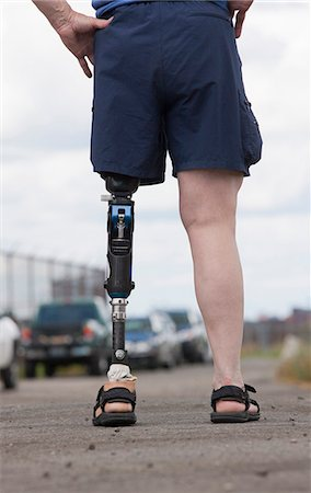 Woman with prosthetic leg standing on the road Stock Photo - Premium Royalty-Free, Code: 6105-05396334