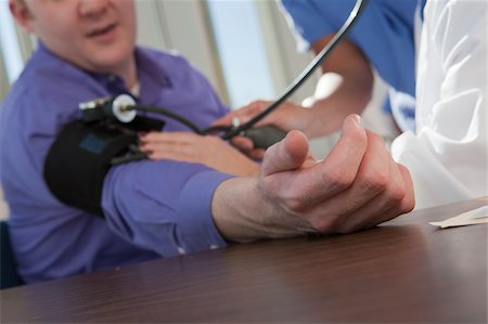 pressure - Female doctor and nurse measuring a patient's blood pressure Stock Photo - Premium Royalty-Free, Code: 6105-05397043