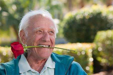 Close-up of a senior man with a romantic rose in his mouth Stock Photo - Premium Royalty-Free, Code: 6105-05397126