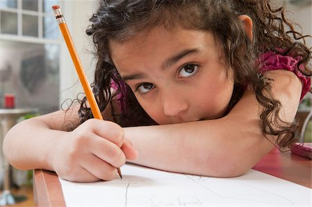 Portrait of a Hispanic girl drawing pictures Stock Photo - Premium Royalty-Free, Code: 6105-05397203