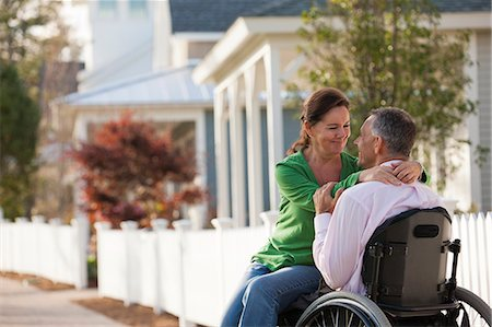 Couple enjoying each other's company in front of their home while he is in a wheelchair Stock Photo - Premium Royalty-Free, Code: 6105-06042943