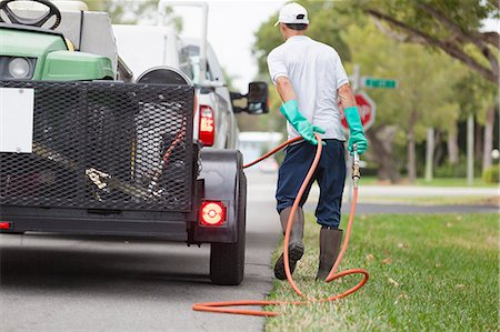 Pest control technician with high pressure spray gun and hose at his truck Stock Photo - Premium Royalty-Free, Code: 6105-06702853