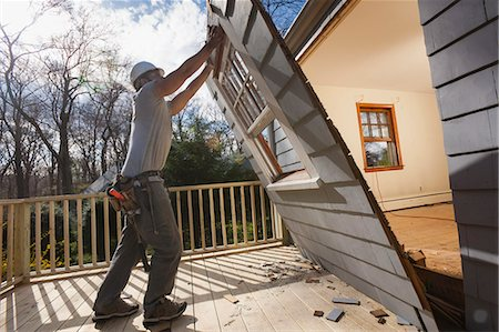 Hispanic carpenter removing newly cut door access to deck on home Stock Photo - Premium Royalty-Free, Code: 6105-06702953