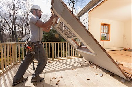 Hispanic carpenter removing newly cut door access to deck on home Stock Photo - Premium Royalty-Free, Code: 6105-06702951