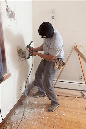 Hispanic carpenter using circular saw to cut wallboard for deck doorway in house Stock Photo - Premium Royalty-Free, Code: 6105-06702938