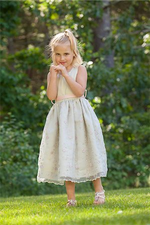 Portrait of a cute little girl standing in a garden Stock Photo - Premium Royalty-Free, Code: 6105-06703014