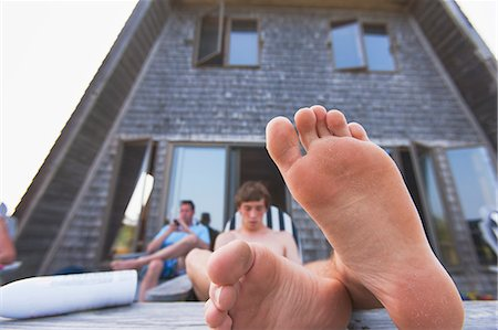 Teenage boy and his father relaxing at a beach house, Block Island, Rhode Island, USA Stock Photo - Premium Royalty-Free, Code: 6105-06703023