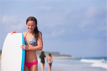 Happy girl with surfboard on the beach, Block Island, Rhode Island, USA Stock Photo - Premium Royalty-Free, Code: 6105-06703151