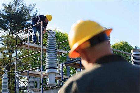 Power engineer performing maintenance on fluid filled high voltage insulator, Braintree, Massachusetts, USA Stock Photo - Premium Royalty-Free, Code: 6105-07521399