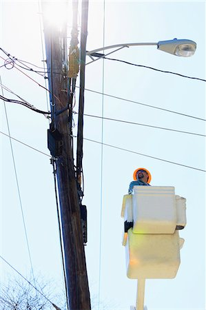 Power engineer riding in lift bucket to work on power lines, Braintree, Massachusetts, USA Stock Photo - Premium Royalty-Free, Code: 6105-07521404
