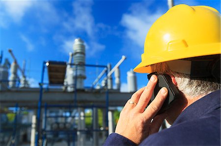 Power engineer talking on a mobile phone at high voltage distribution station, Braintree, Massachusetts, USA Stock Photo - Premium Royalty-Free, Code: 6105-07521408
