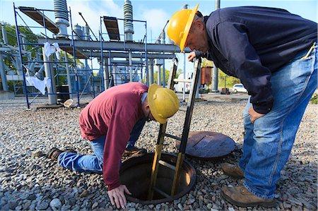 Power engineers placing ladder inside manhole at high voltage power distribution station, Braintree, Massachusetts, USA Stock Photo - Premium Royalty-Free, Code: 6105-07521409