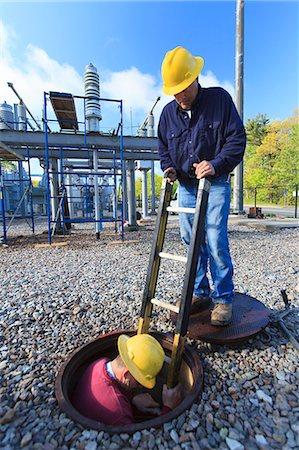 Power engineer entering manhole at a high voltage power distribution station, Braintree, Massachusetts, USA Stock Photo - Premium Royalty-Free, Code: 6105-07521410