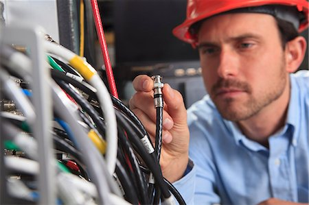 fibre optic - Network engineer holding BNC cable connection at patch panel Stock Photo - Premium Royalty-Free, Code: 6105-07744487