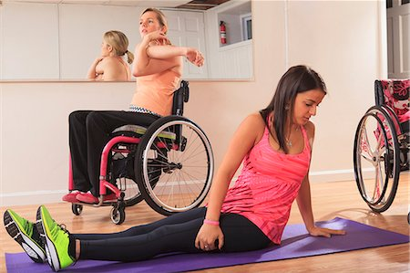 disable exercising - Young women with spinal cord injuries stretching in a yoga studio Stock Photo - Premium Royalty-Free, Code: 6105-07744421