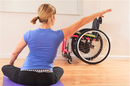 disable exercising - Young woman with a spinal cord injury doing a yoga pose in a studio Stock Photo - Premium Royalty-Free, Code: 6105-07744426