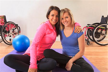 disable exercising - Young women with a spinal cord injuries arm in arm and with their wheelchairs in a yoga studio Stock Photo - Premium Royalty-Free, Code: 6105-07744429