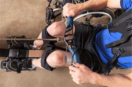 rehabilitation - Man with spinal cord injury using his rowing machine with a muscle stimulator attached Stock Photo - Premium Royalty-Free, Code: 6105-07744516
