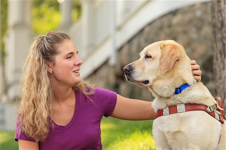Woman with visual impairment petting her service dog Stock Photo - Premium Royalty-Free, Code: 6105-08211242